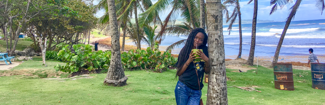 Clorissa Williams standing in front of the beach at the  University of West Indies Barbados